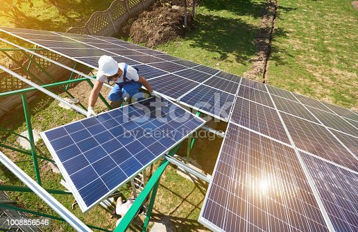 istock Professional worker installing solar panels on the green metal construction 1008856546