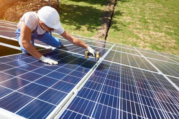 在綠色金屬建築上安裝太陽能電池板的專業工人 - 太陽能電池板 個照片及圖片檔