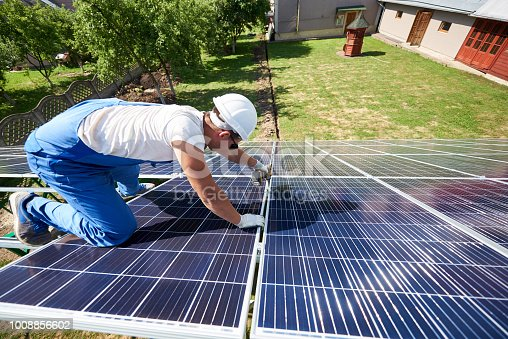 istock Professional worker installing solar panels on the green metal construction 1008856602