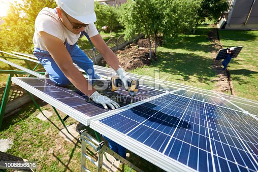 istock Professional worker installing solar panels on the green metal construction 1008856616