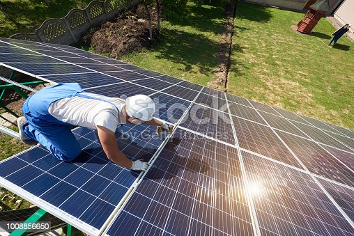 istock Professional worker installing solar panels on the green metal construction 1008856650
