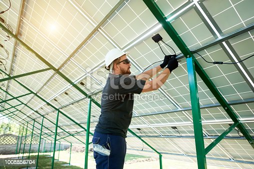 istock Professional worker installing solar panels on the green metal construction 1008856704