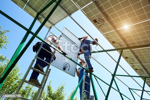 istock Professional worker installing solar panels on the green metal construction 1008856790