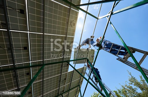 istock Professional worker installing solar panels on the green metal construction 1008867666