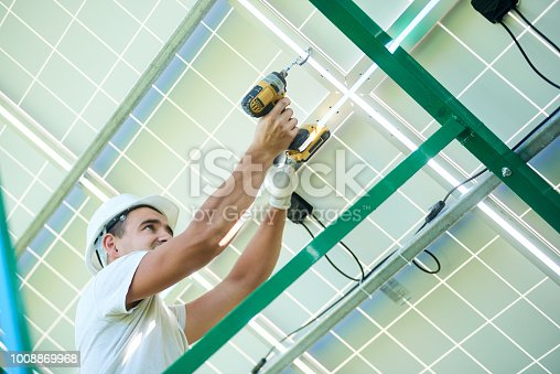 istock Professional worker installing solar panels on the green metal construction 1008869968