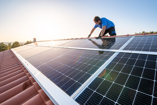 kneeling professional fixing solar panels from the top of a house roof, side view of the roof with sun reflection