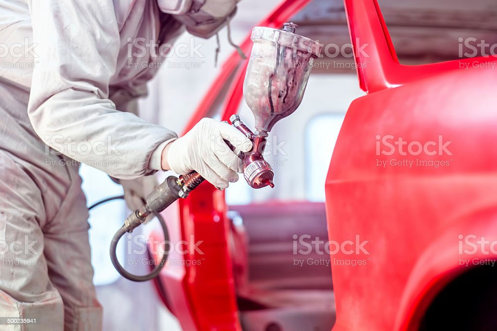 Professional worker spraying red paint on a car body stock photo