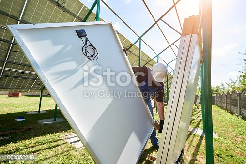 istock Professional worker wearing white protective helmet, mounting solar pannels on metal construction 1008852246