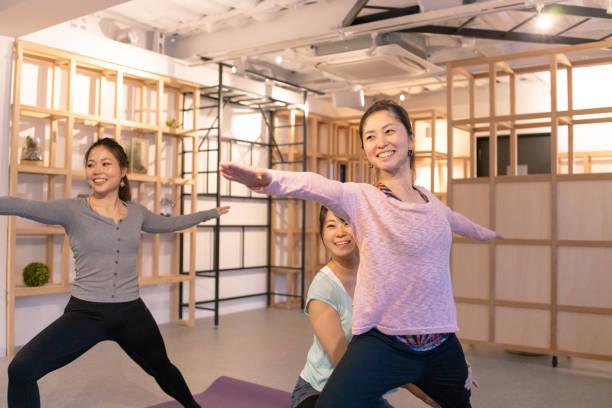 健康クラブで女性を支えるプロのヨガインス トラクター - スタジオ 日本人 ストックフォトと画像
