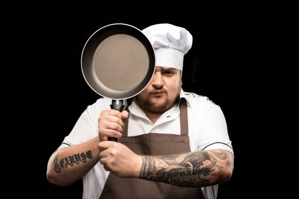 professional young chef in hat and apron holding frying pan isolated on black stock photo