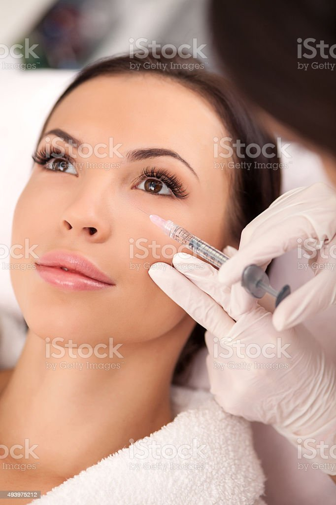 Professional young cosmetician is serving her patient stock photo