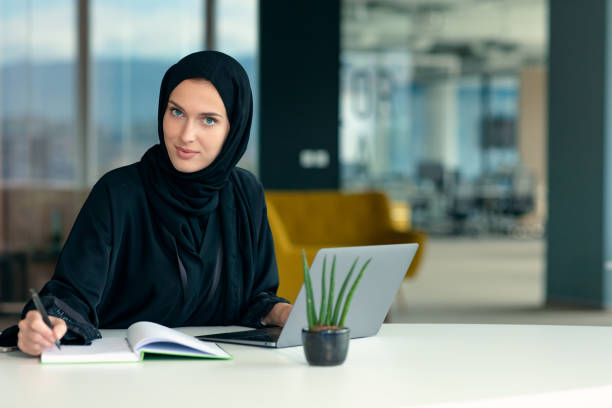 professional young muslim business woman using mobile digital tablet computer at work stock photo