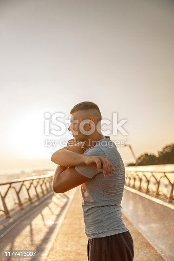 Side view of a Caucasian young athlete doing stretching exercises on a bridge