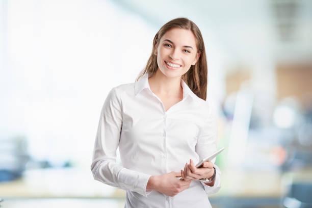 デジタル タブレットを持つプロの若い女性 - 襟付きシャツ ストックフォトと画像