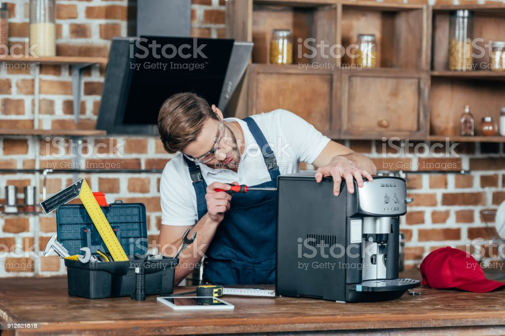 professional young worker in eyeglasses and protective workwear fixing coffee machine stock photo