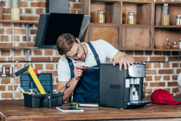 professional young worker in eyeglasses and protective workwear fixing coffee machine - coffee maker stock pictures, royalty-free photos & images