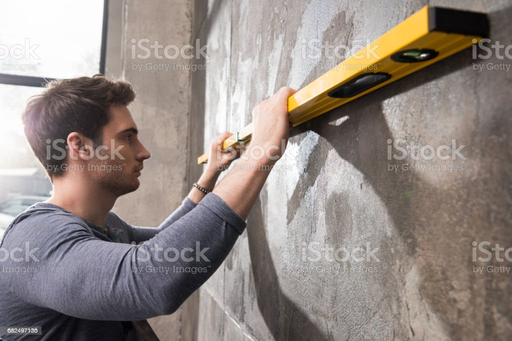 Professional young worker measuring wall with level tool, renovation concept foto de stock royalty-free
