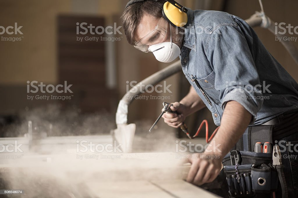 Professionally dressed carpenter varnishing board stock photo