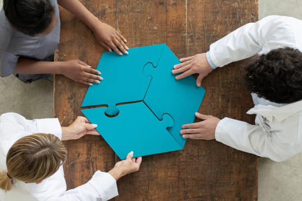 Professionals assembling 3 par puzzle piece, aerial view stock photo