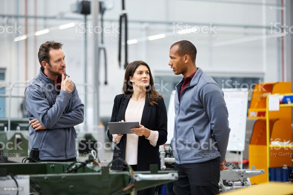 Professionals discussing in car factory stock photo