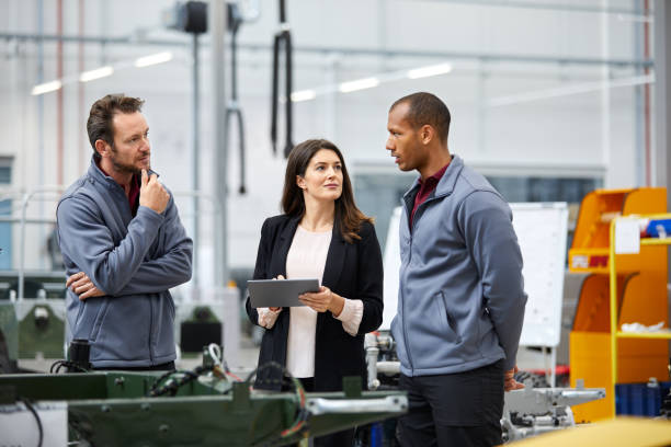 professionals discussing in car factory - quality control stock photos and pictures