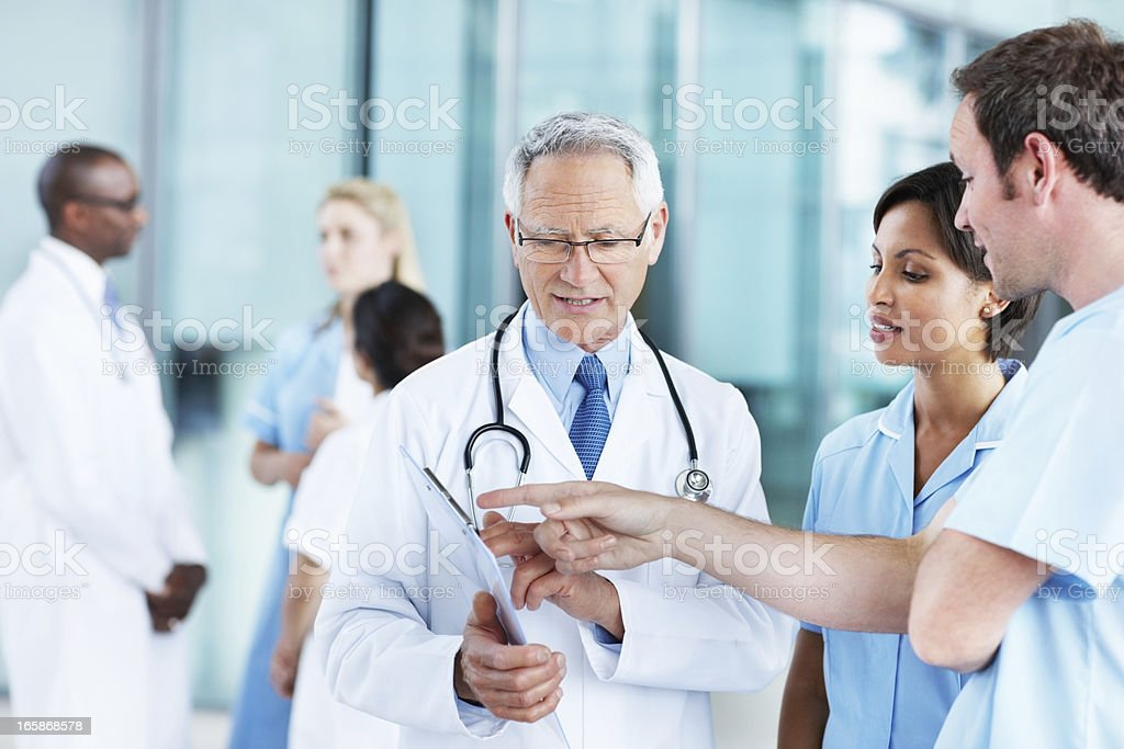Professionals discussing patient's medical report royalty-free stock photo