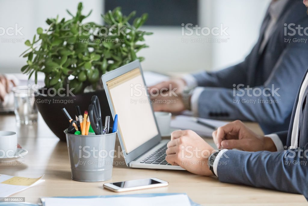 Professionals in meeting room with laptop Close up of businessman sitting at conference table and working on laptop with colleague in background. Adult Stock Photo
