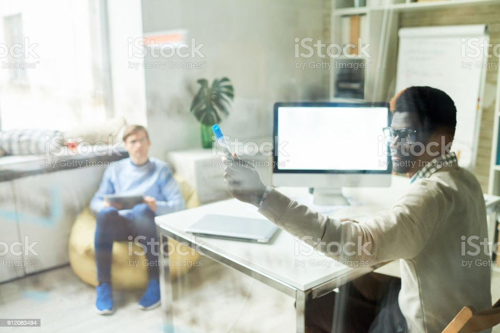Portrait of African IT professional working in web studio pointing to...