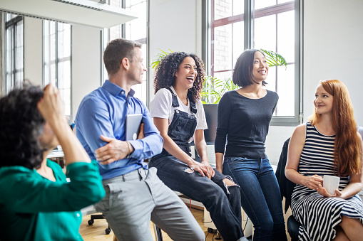 Cheerful multi-ethnic business colleagues in meeting. Male and female professionals laughing during a meeting.