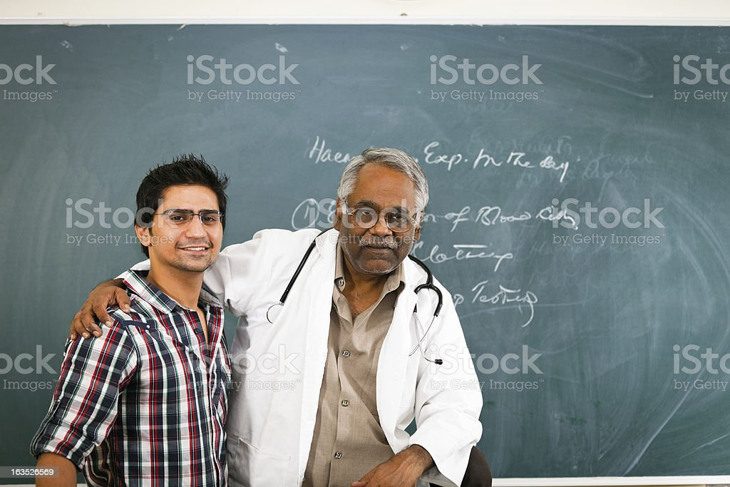 professor and his student in front of a chalkboard stock photo
