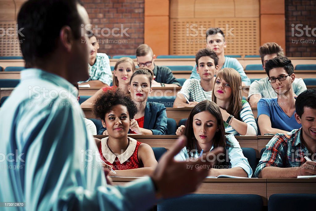 Professor giving a lecture Large group of students sitting in the lecture hall at university and listening to their teacher. Focus on the audience. 20-24 Years Stock Photo