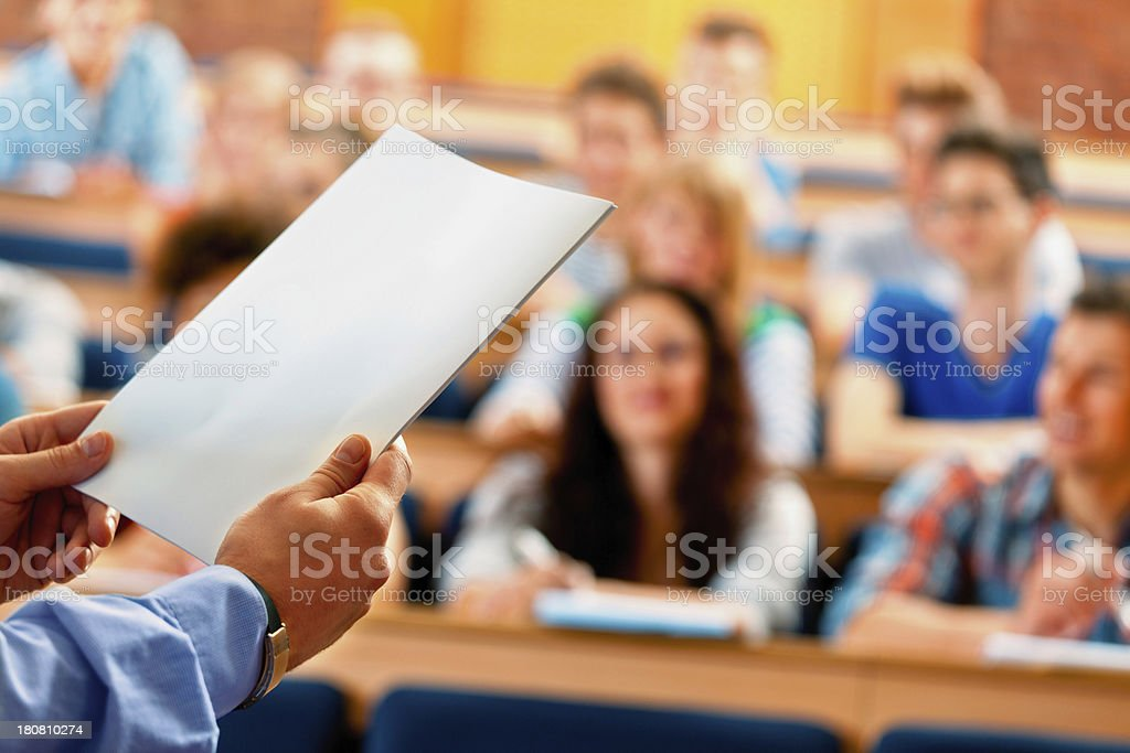 Professor giving a lecture Large group of students sitting in the lecture hall at university and listening to their teacher. Focus on the professor's hand holding piece of paper. 20-24 Years Stock Photo