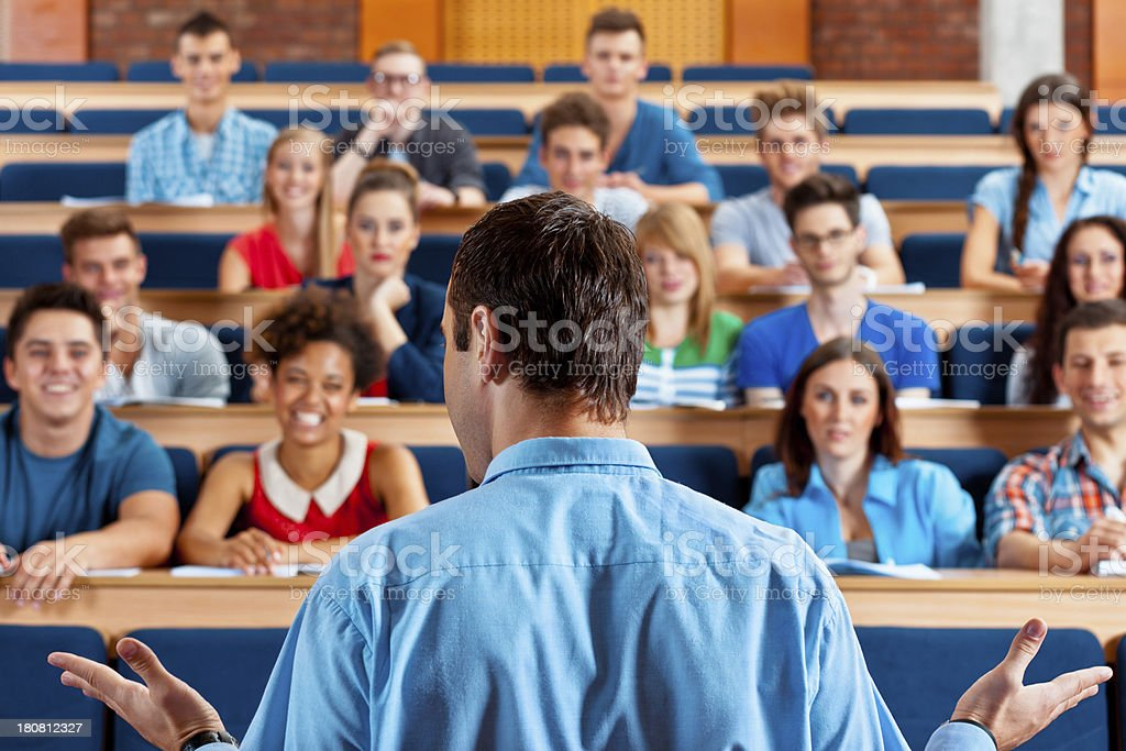 Professor giving a lecture Large group of students sitting in the lecture hall at university and listening to their teacher. Focus on the professor. 20-24 Years Stock Photo