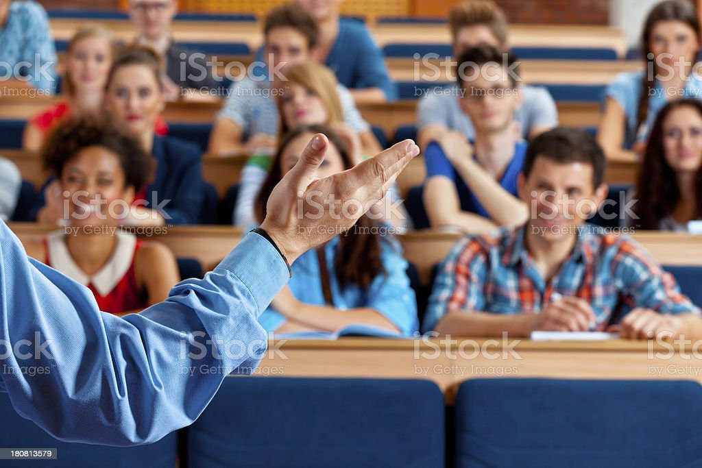 Professor giving a lecture Large group of students sitting in the lecture hall at university and listening to their teacher. Focus on the professor's hand. 20-24 Years Stock Photo