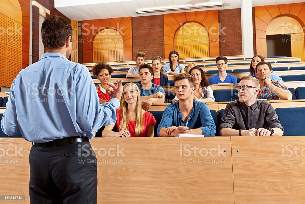 Professor giving a lecture Large group of students sitting in the lecture hall at university and listening to their teacher.  20-24 Years Stock Photo