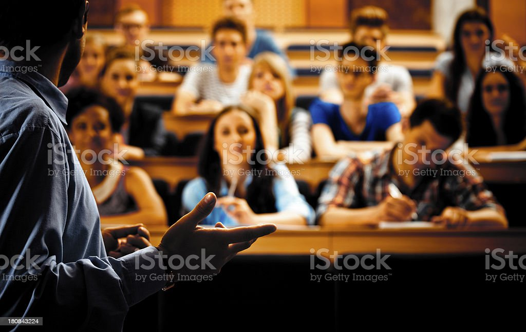 Professor giving a lecture Large group of students sitting in the lecture hall at university and listening to their teacher. Focus on the professor. Dark tones. 20-24 Years Stock Photo