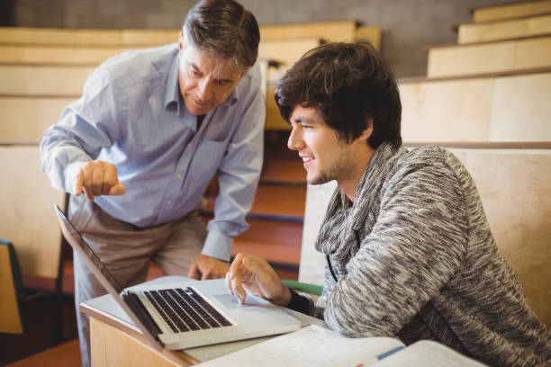 professor helping a student in classroom - professor stock photos and pictures
