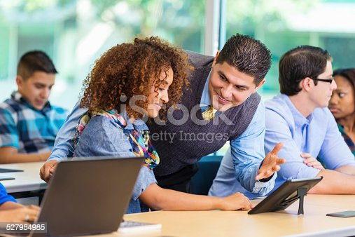 485539628 istock photo Professor helping college freshman with digital tablet in classroom 527954985