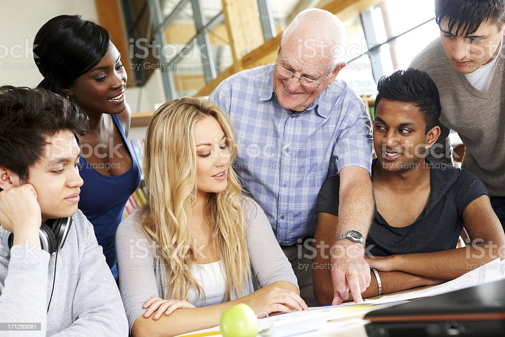 Professor helping students with their assignments royalty-free stock photo