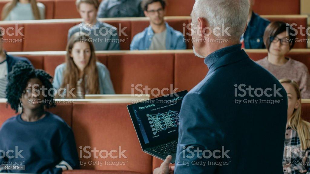 Profesor de Ciencias de la computación Lee Conferencia a un aula llena de estudiantes Multi étnica. Profesor tiene Laptop con el aprendizaje profundo, infografía de Inteligencia Artificial en la pantalla. foto de stock libre de derechos