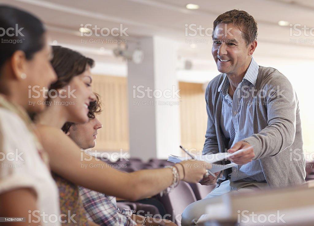 Profesor de la devolución de los deberes a estudiantes universitarios en conferencia h - foto de stock