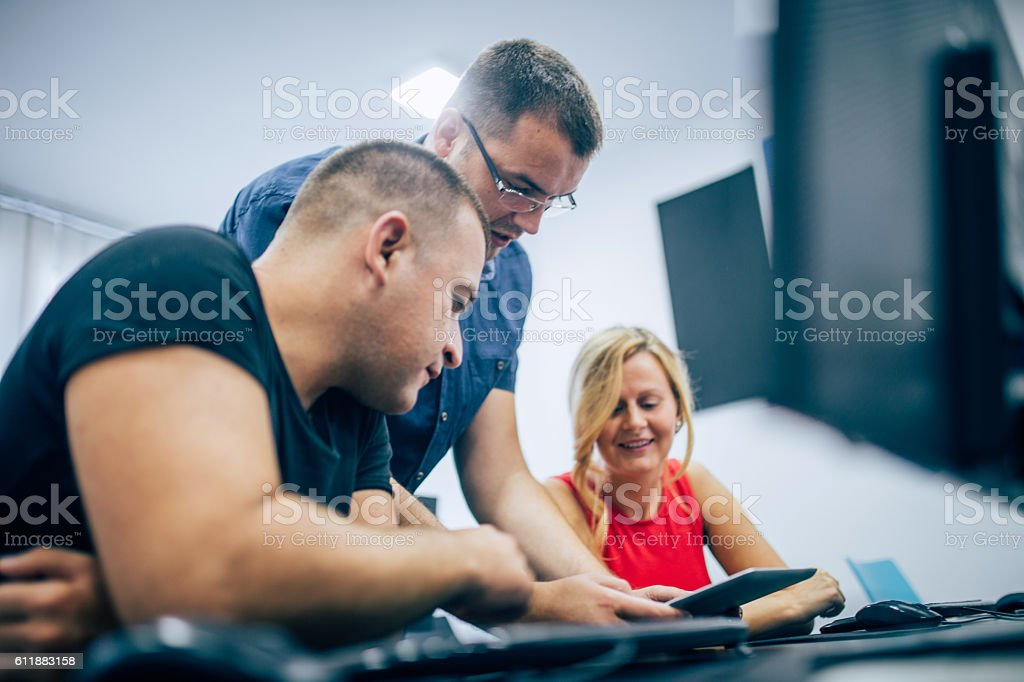 Professor showing students how to use tablet stock photo