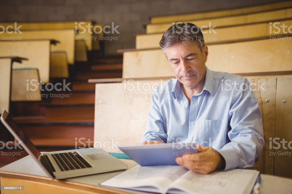 Professor sitting at desk using digital tablet Professor sitting at desk using digital tablet in classroom 50-54 Years Stock Photo