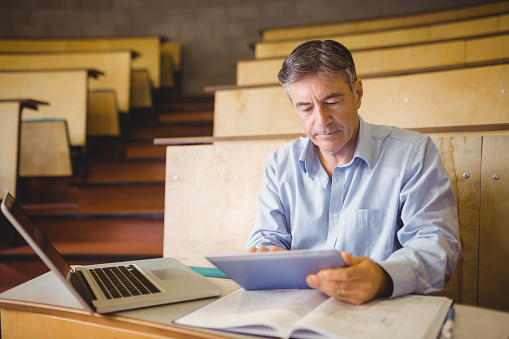 Professor Sitting At Desk Using Digital Tablet Stock Photo - Download Image Now