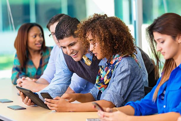 professore insegnare gruppo eterogeneo di studenti utilizzando la tecnologia moderna - professore di scuola superiore foto e immagini stock