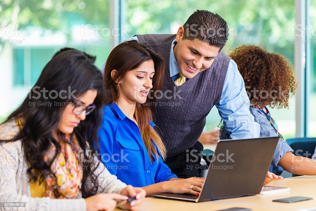 Professor teaching student with laptop in college classroom stock photo
