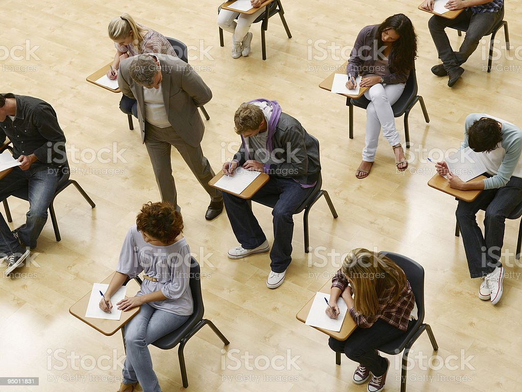 Professor walking by college students taking test in classroom stock photo