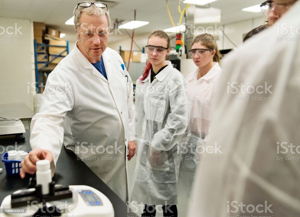 Professor with group of students in College pharmaceutical laboratory. stock photo