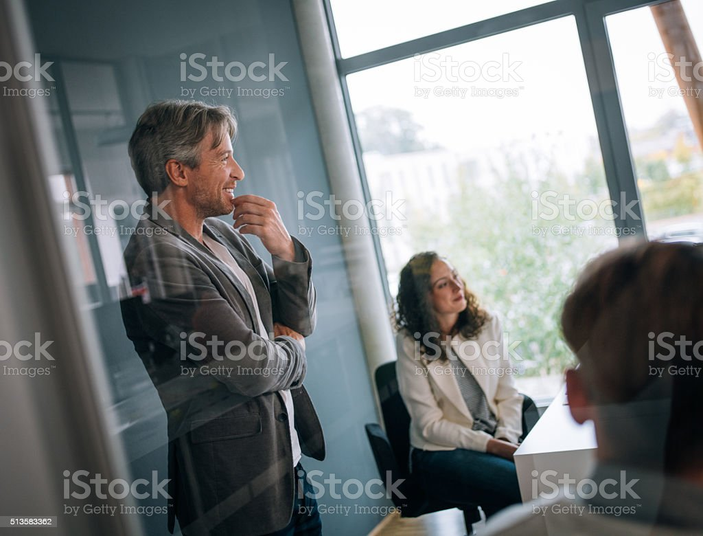 Proffessional team leader smiling in group meeting stock photo