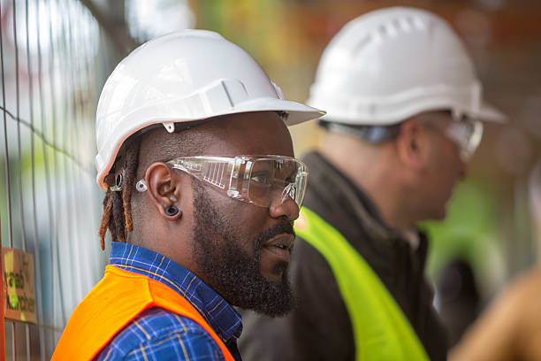 Profile close up of two engineers wearing protective hardhats stock photo